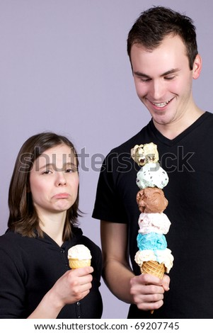 Young man joyously holds a six scoop ice cream cone while a young lady frowns at her single scoop plain vanilla ice cream cone.