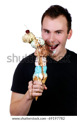 Young man joyously licks a six scoop ice cream cone as it drips all over.