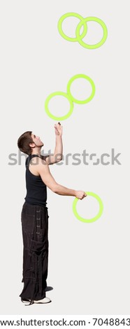 Young man juggling five rings.