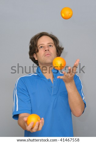 Young man juggling with oranges