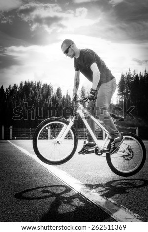 Young man jump on bicycle through the white line.  Black and white tonality
