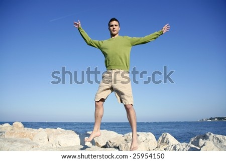 Young man jump over stones in ocean blue shore, sunny summer day