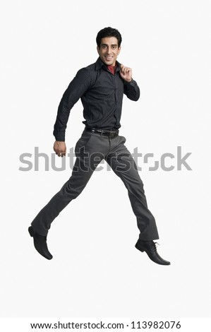 Young man jumping against a white background