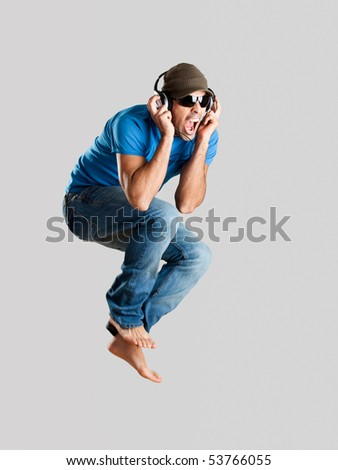 Young man jumping and listening music isolated over a gray background