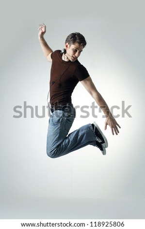 Young man jumping and listening music on light background