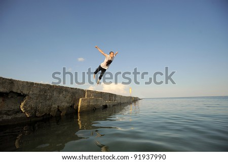 Young man jumping from a pier inro the water