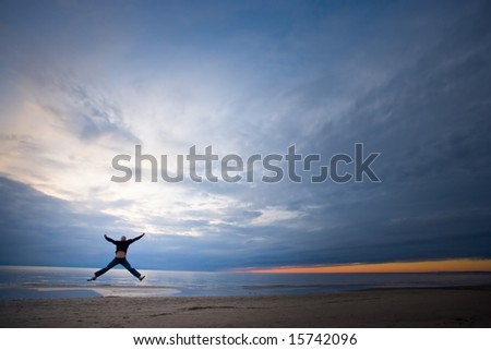young man jumping high on the seashore