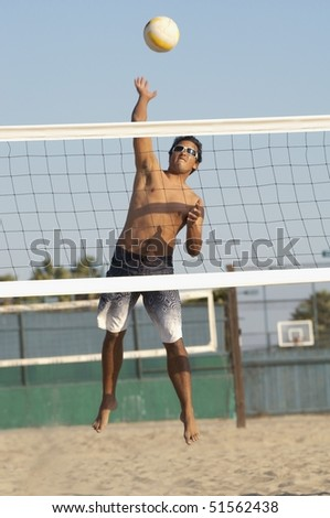 Young man jumping, hitting volleyball over net on beach