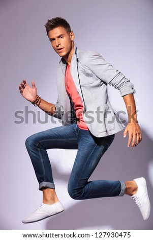 young man jumping in the air in a running position, looking at the camera, over light background
