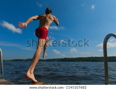 Young man jumping into water. Boy diving from pier. Summer time sport activity. - Shutterstock ID 1145107682