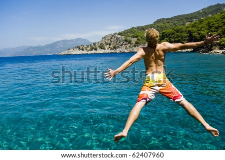 Young man jumping off a boat, enjoying the freedom of his summer holiday - stock photo