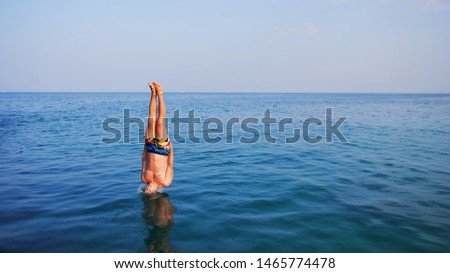 Young man jumping off cliff into blue water ocean at sunset. Active outdoor, holiday adventure, tourism action, healthy summer joy, Fun activity lifestyle. Crazy adult guy in swimwear fly from climb