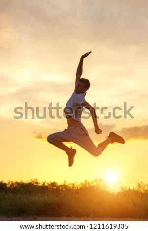 young man jumping up against the sunset sky. #1211619835