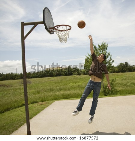Young man jumping up to rebound a goal on a bright sunny day on an outdoor basketball court.
