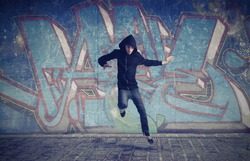 Young man jumping with a graffiti in the background