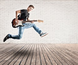 young man jumping with electric guitar on a room
