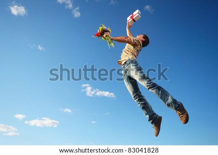 Young man jumping with flowers and gift box on blue sky background