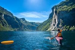 young man kayaking along the fjord geiranger enjoying the waterfall