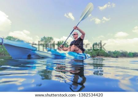 Young Man Kayaking on Lake. Lake Kayaking.