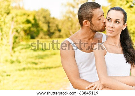 Young man kisses in on cheek beautiful dark-haired woman, against summer solar park. - stock photo