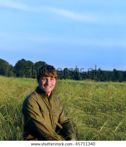Young man kneels in a meadow near sunset.  He is smiling happily and wearing jeans and olive long sleeved shirt.