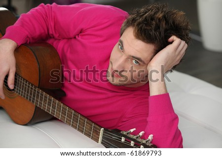 Young man laid near a guitar