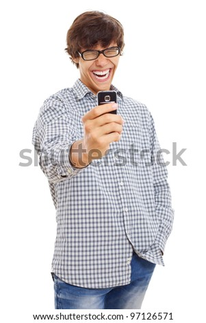 Young man laughing and filming something funny on his mobile phone. Isolated on white background, mask included