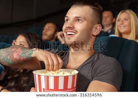 Young man laughing during a comedy film