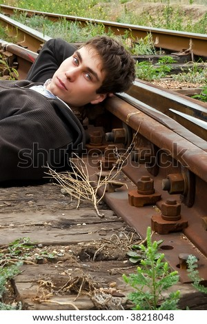 Young man laying on a railway tracks looking at you
