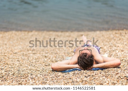 Young man laying on the sandy beach next to a coastline, sunbathing and enjoying vacations #1146522581