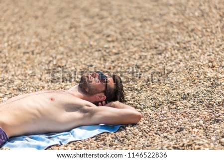 Young man laying on the sandy beach next to a coastline, sunbathing and enjoying vacations #1146522836