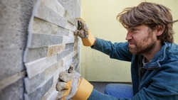 Young man laying ornamental tiles on an outside wall.