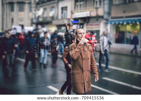 Young man leading a protest march. Riot on the streets of a city. Rebellion, protest, riot, student march, rebellious youth, anti-government and anti-dictatorship concepts.