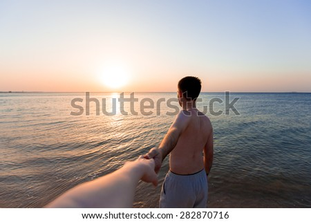 Young man leading by hand his lover, at the sea coast in sunlight, follow me concept