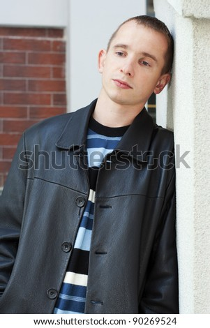 Young man leaning against the wall and looking down