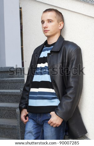 Young man leaning against the wall and waiting