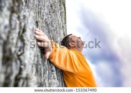 Young man leaning on rock of steep mountain climb with hands wide open.