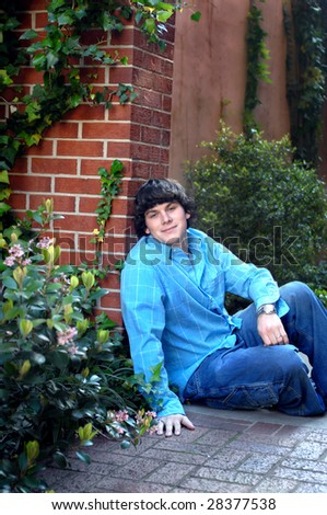 Young man leans against a brick wall in a garden.  He is wearing jeans and a blue shirt.