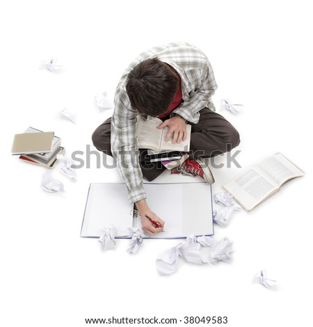 Young man learning surrounded by books, exercise books and crushed paper