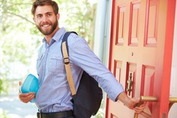 Young Man Leaving Home For Work With Packed Lunch