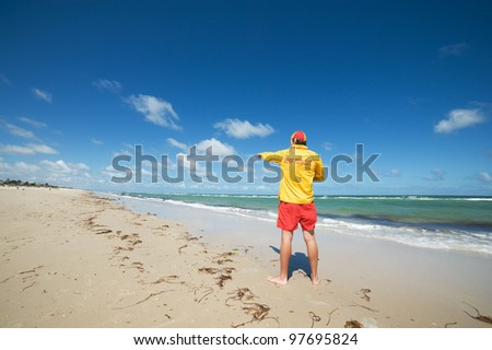 young man  life saver  watching the situation on the sea