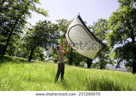 Young man lifting dome tent above head on camping trip in woodland clearing, side view (tilt)