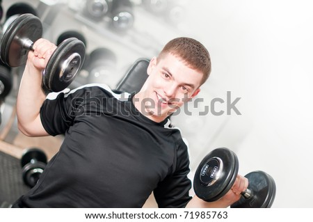 Young man lifting dumbbells in sport club. White background