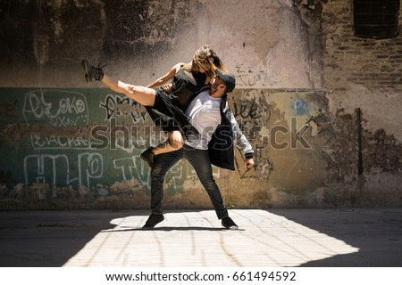 Young man lifting her dancing partner and both looking at each other while performing a dance routine