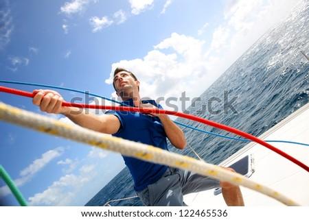 Young man lifting the sail of catamaran during cruising