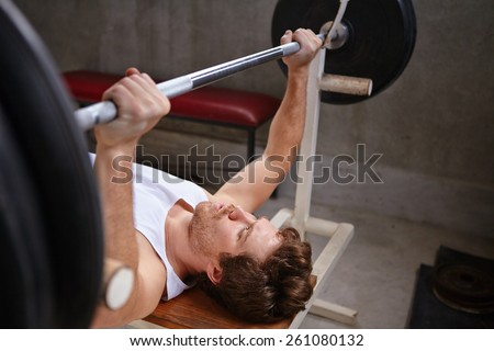 Young man lifting up weights in a private gym