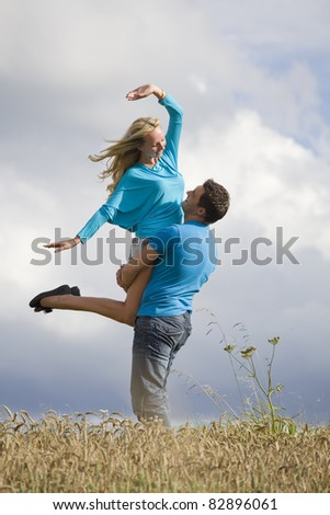 young man lifting woman in countryside