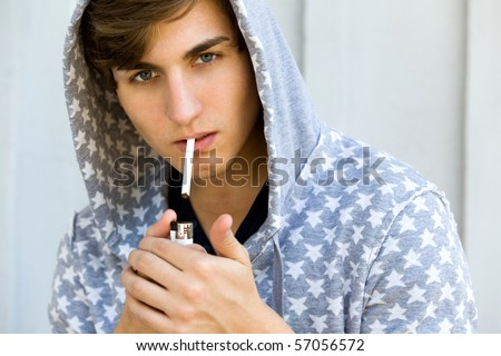 Young Man Lighting A Cigarette