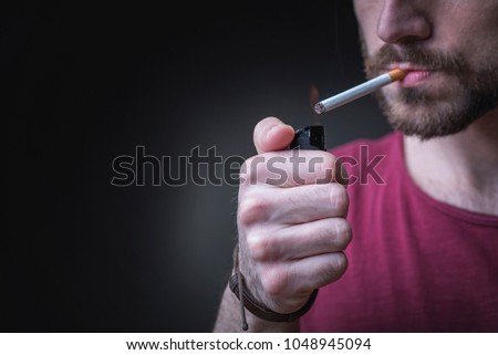 Photo of Young man lighting a cigarette, studio image, dramatic lighting
