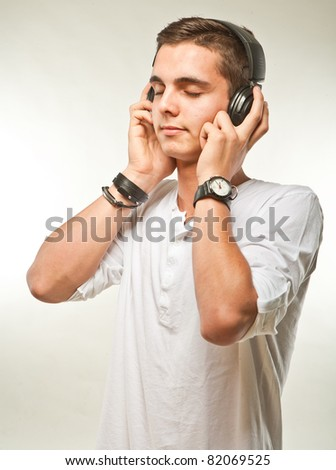 Young man listening music on his headphones. Candid picture.
